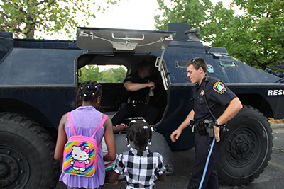 Officers showing civillians inside of large vehicle