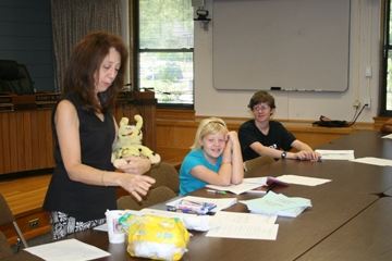 A woman and two young children looking at papers on a table
